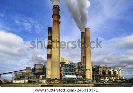 An interesting view of smoke stack at a power plant. - stock photo