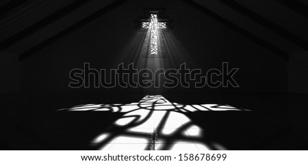An interior building with a crucifix shaped stained glass window with a spotlight rays penetrating through it reflecting the image on the floor - stock photo
