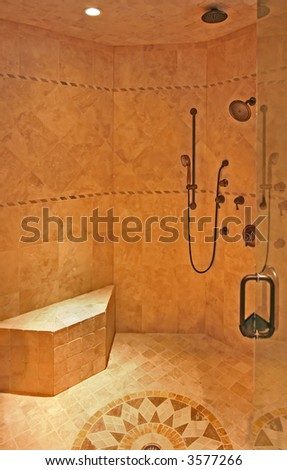 An interior of a fancy shower stall with seating and multiple shower heads.