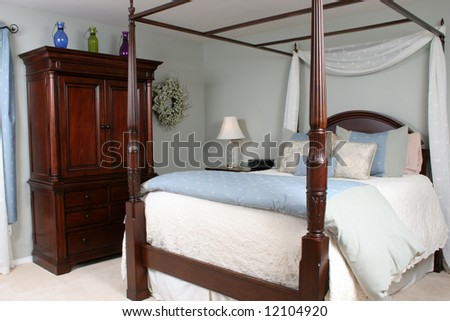 An interior of a master bedroom with a four poster bed and beautiful cherry wood furniture. - stock photo