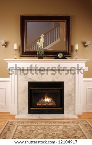 An interior shot of a marble fireplace with beautiful woodwork,a framed mirror and warm inviting colors. - stock photo