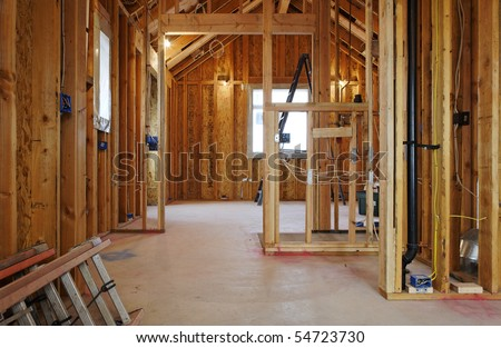 An interior view of a new home under construction with exposed wiring and and a ladder on the floor. Horizontal shot.