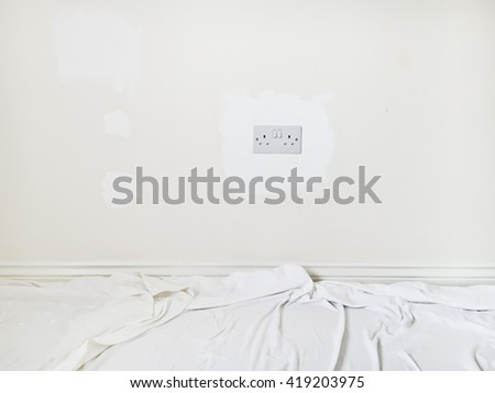 An interior wall being painted white