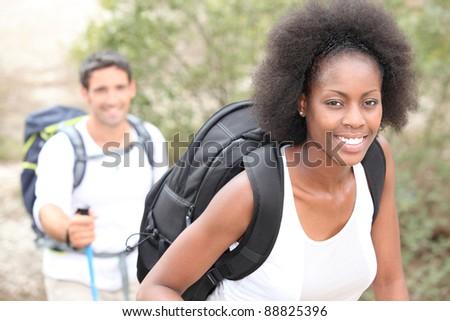 An interracial couple mountain hiking. - stock photo