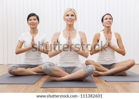 An interracial group of three beautiful young women sitting cross legged in a yoga position at a gym - stock photo