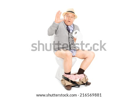 An interrupted senior sitting on a toilet isolated on white background - stock photo