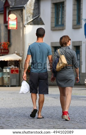 An Intimate couple casually dressed strolling down the street in the evening