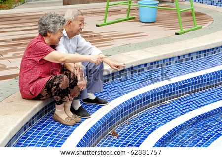an intimate senior couple sitting beside a pool - stock photo