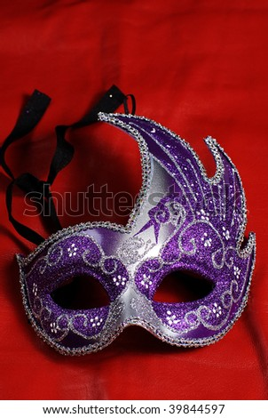 An intricate halloween mask shot against a red background - stock photo