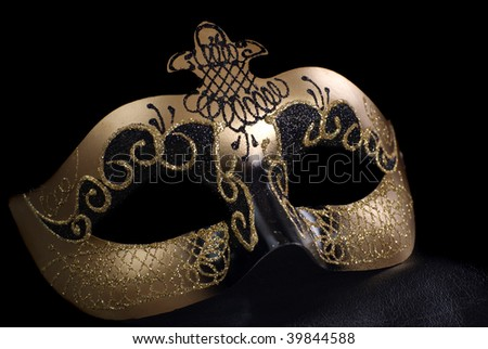An intricate venetian mask, shot against a black background