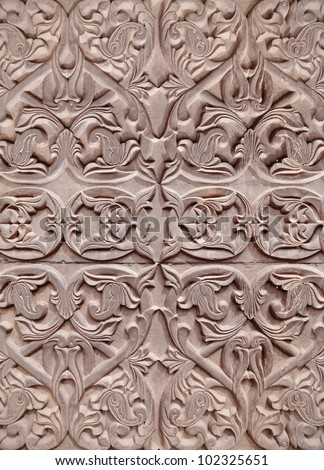 An intricate vine pattern on a grungy ornamental clay tablet for textural background. - stock photo