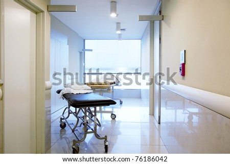 An intrior of a hospital hallway with a couple stretchers - stock photo