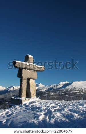 An inukshuk a traditional native sculpture, stands on Whistler Mountain overlooking Blackcomb.