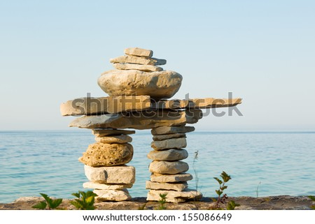 An inukshuk on a shore of Lake Huron, Bruce Peninsula, Ontario, Canada - stock photo