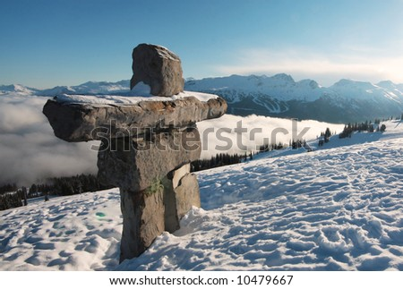 An inukshuk stands sentry over Whistler and Blackcomb mountain, British Columbia,  Canada. - stock photo
