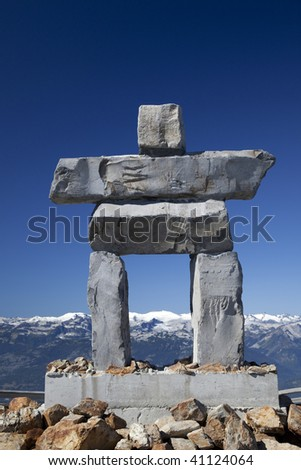 An Inukshuk towers over the surrounding snow capped Coastal mountains. - stock photo