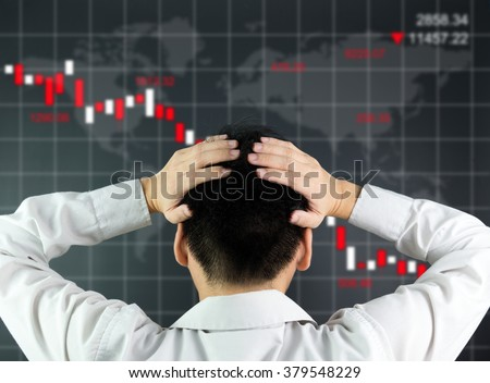 An investor is looking at screen showing stock market crash - stock photo