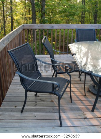 An inviting chair pulled out from the table on a deck in the woods - stock photo