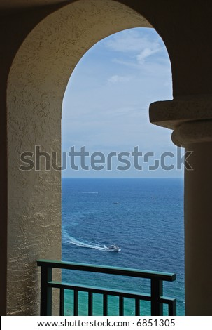 An inviting view of a boat on the ocean through an arch of a balcony. - stock photo