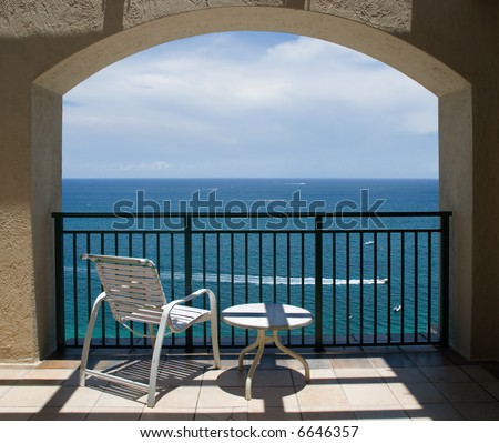 An inviting view of the ocean and a boat through an arch of a balcony. - stock photo