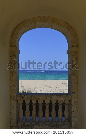 An inviting view of the ocean and a boat through an arch of a worth avenue clock tower at Palm Beach, Florida, United States - stock photo