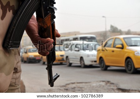 An Iraqi soldier armed with an assault rifle pointed to the ground watching traffic flow by at a roadblock in Baghdad. Narrow DOF, vehicles blurred. - stock photo