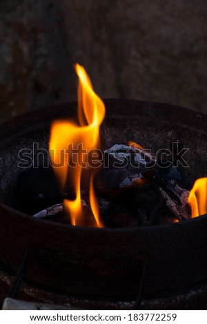 An iron bucket full of charcoal dark with some flames ember and ash - stock photo