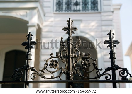 an iron fence in front of an antebellum mansion in the New Orleans Garden District - stock photo