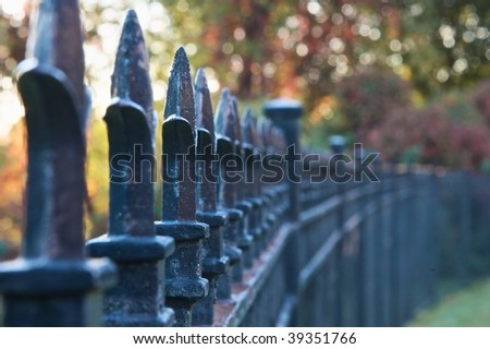 An iron fence with fall foliage in the background (http://www.artistovision.com/outdoors/iron_fence.html). - stock photo