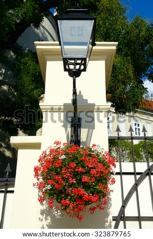 an iron light post adorned with red-white geranium hanging baskets - stock photo