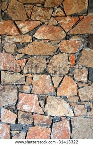 An irregular assortment of a stone wall background - stock photo