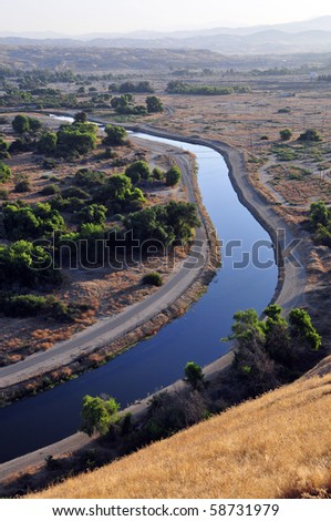 An irrigation canal distributing water to farms in the San Joaquin Valley, California - stock photo