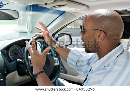 An irritated business man driving a car is expressing his road rage with his hands in the air.