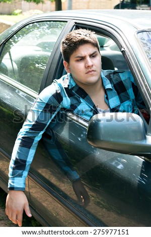 An irritated young man driving a vehicle with his head and arm hanging out of the window. - stock photo