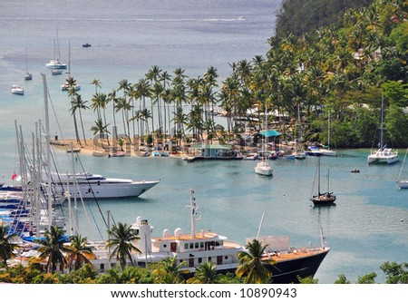 An island harbor and bay full of boats and palm trees - stock photo