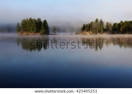 An island reflecting in Sunbeam Lake in Algonquin Provincial Park, Ontario, Canada.  - stock photo