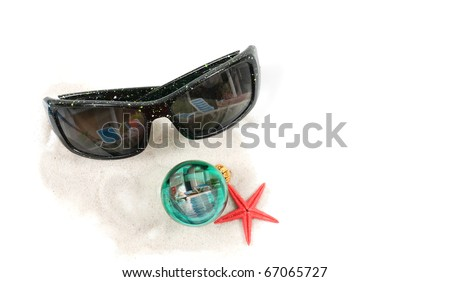 An isolated angled closeup view of a pair of sunglasses, christmas bulb, red star fish, on some white sand. Pool reflections in the Christmas bulb and sunglasses. - stock photo
