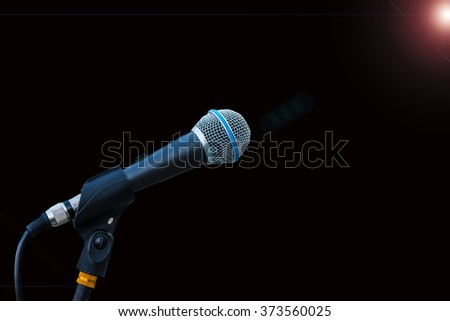 An isolated classic microphone on a black background with flare