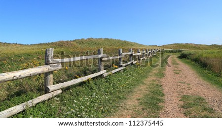 An isolated dirt road through rural Prince Edward Island. - stock photo