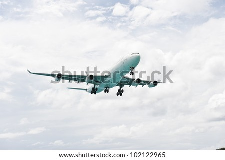 An isolated image of an airplane flying in a cloudy sky.