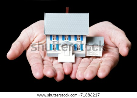An isolated pair of womans hands holds a toy house. - stock photo