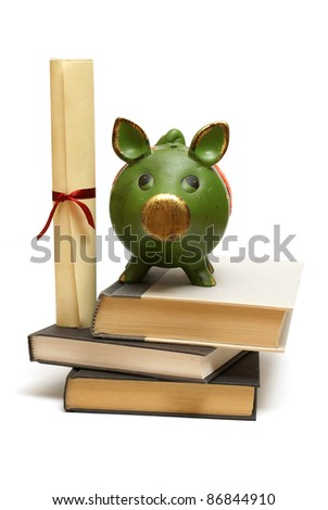 An isolated pig bank and diploma scroll represent educational finances. - stock photo