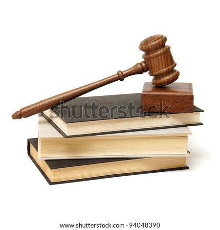 An isolated pile of books with a wooden gavel resting on top. - stock photo