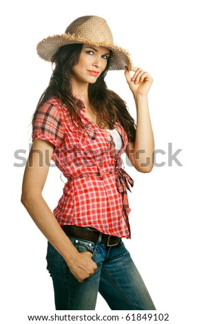 An isolated portrait of a beautiful young cowgirl with attitude holding her hat. Isolated over white. - stock photo