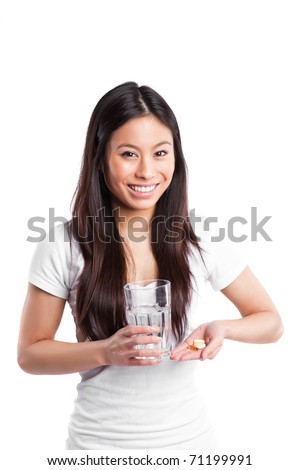 An isolated shot of a beautiful asian woman taking her vitamins