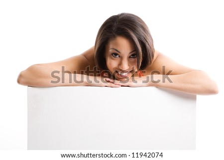 An isolated shot of a beautiful woman smiling and showing an empty billboard - stock photo