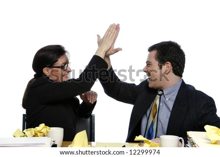 An isolated shot of a businessman and businesswoman giving each other a high five at a desk, littered with yellow paper. - stock photo