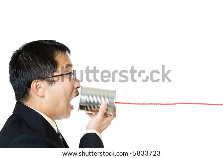 An isolated shot of a businessman communicating with a tin can phone - stock photo