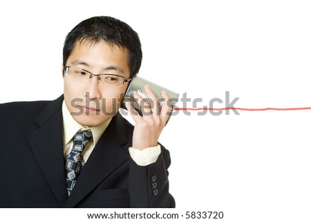 An isolated shot of a businessman listening to a tin can phone - stock photo