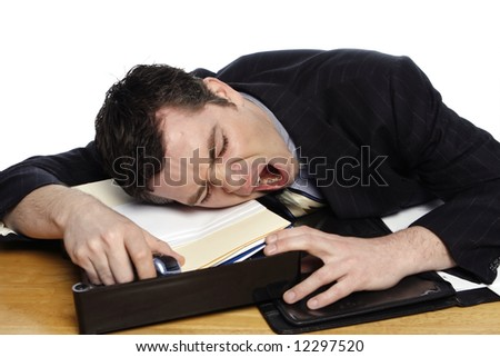 An isolated shot of a businessman lying his head down on desk yawning. - stock photo